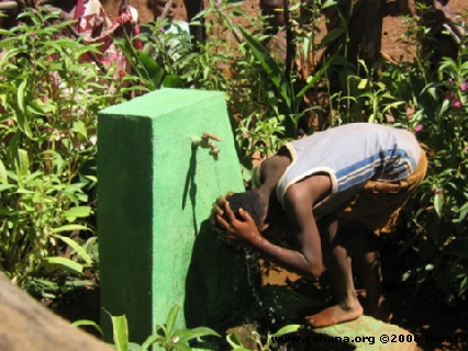 boy washing hair at water faucet in Madagascar