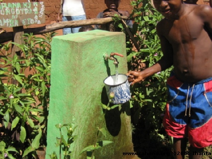 Boy getting clean water from a faucet in Madagascar
