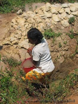 woman with bucket in water hole_in_Fiadanana_Madagascar